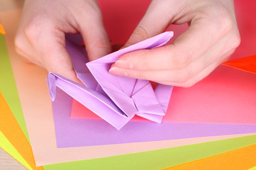Hands making origami crane, close up