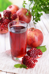 Ripe pomegranates with juice on table on light background