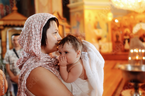 in the church against the icons and lights woman holding a cute