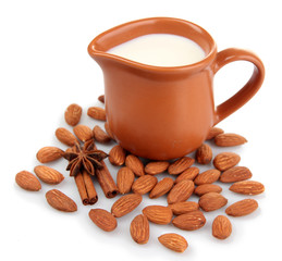 Almond milk in jug with almonds, isolated on white
