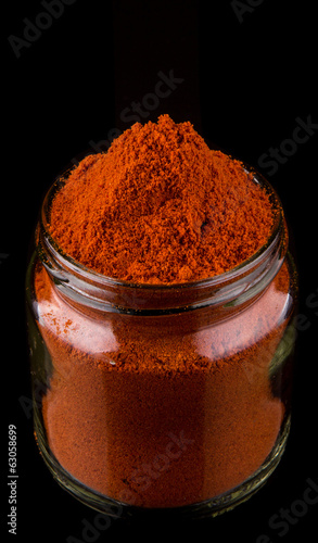 Powdered red chili spices over black background