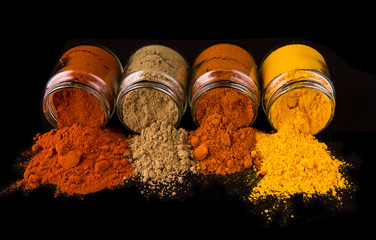 Mix powdered spices in glass container over black background
