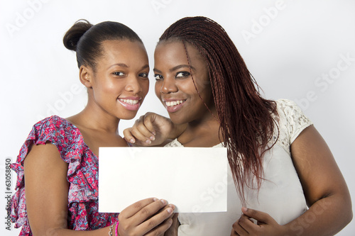 African American friends hold white board together