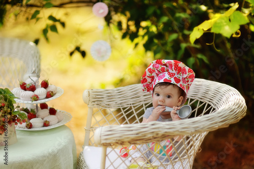 Outdoors in the garden on a wicker chair cute girl in toque