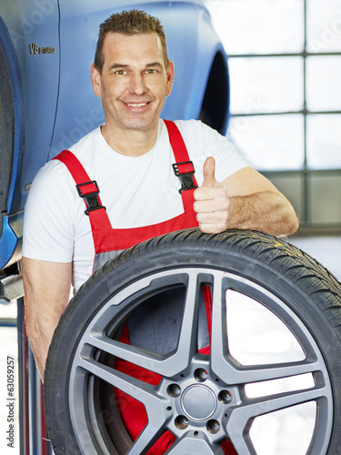 Master mechanic shows thumb up in a garage