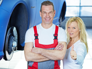 Female customer and mechanic in front of a car