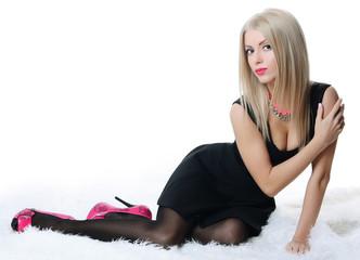 Beautiful sensual woman in a black dress on a carpet