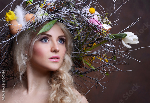 The beautiful girl with a wreath from branches and flowers