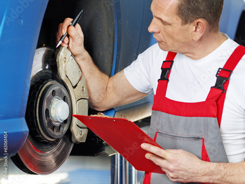 Car mechanic looking at repair costs for a bracke
