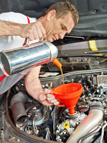 Motor mechanic changes the oil of a car