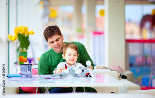 father and son playing toys together in cafe