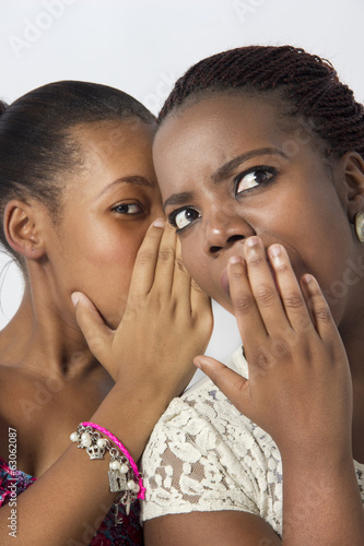 Two Female Friends Gossiping behind their hands