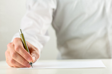 Man writing with a fountain pen on blank paper