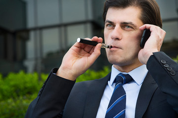 Businessman is smoking electronic cigarette