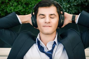 Businessman is relaxing in headphones