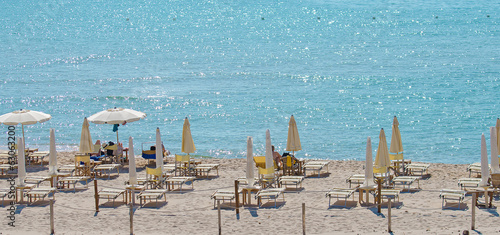 Tropical beach with deckchairs, umbrellas and people.