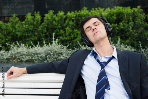 Businessman is relaxing in headphones on the bench