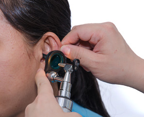 ENT physician checking patient's ear using otoscope with an inst
