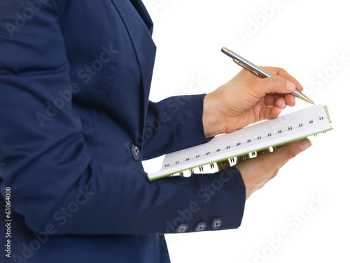 Closeup on business woman writing in notepad