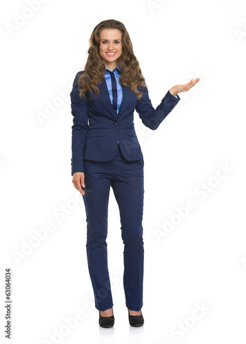 Full length portrait of business woman pointing on copy space