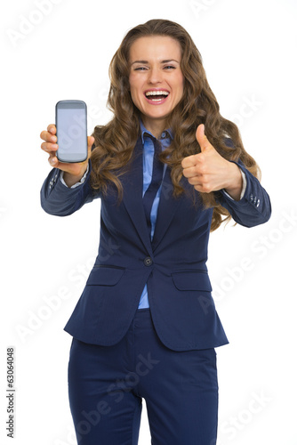 Happy business woman showing phone and thumbs up