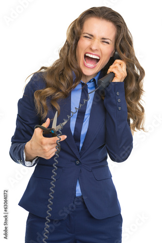 Business woman cutting phone handset with scissors