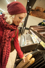 young woman buying baguette in the supermarket