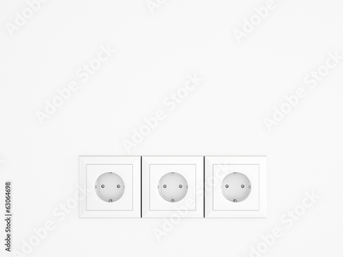 White wall with three european electric outlets.Conceptual.