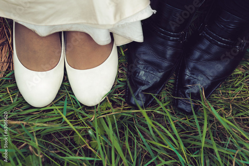 wedding shoes of bride and groom in a green grass
