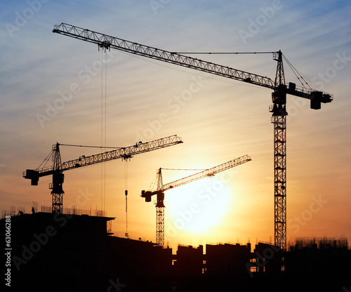 Staande foto Industrial geb. Silhouettes of construction cranes against the evening sky