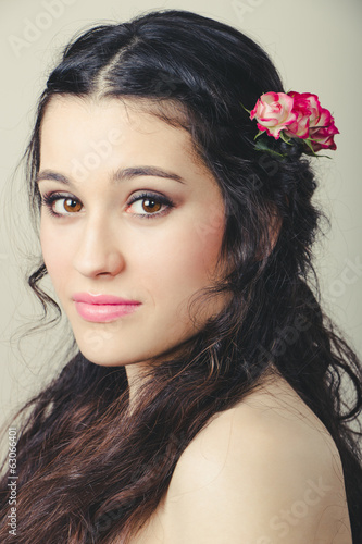 Beautiful brunette with roses in hair
