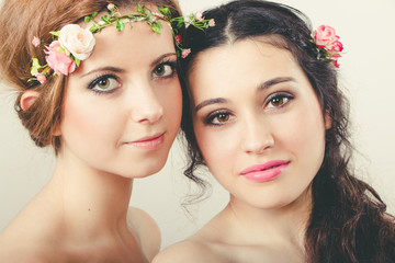 Two beautiful girls with flowers in head