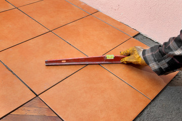 Home renovation, worker control tiles with level tool