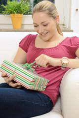 Frau öffnet Geschenk zu Geburtstag