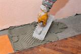 Home renovation, trowel spreading mortar for ceramic tile
