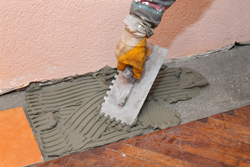 Home renovation, trowel spreading mortar for ceramic tile