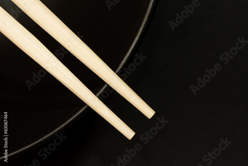 Two chopsticks on top of a black bowl
