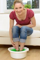 Frau nimmt erholsames Fußbad