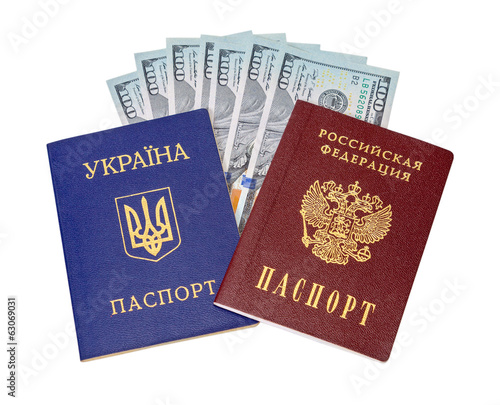 Ukrainian, Russian passports and  dollar bills over white backgr