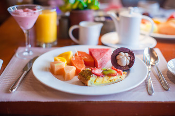 Philippino healthy breakfast with juicy fruits and black coffee