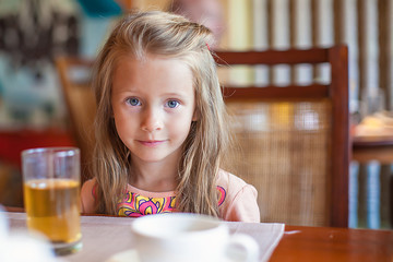 Fashion little girl having breakfast at resort restaurant