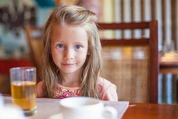 Fashion little girl having breakfast at resort restaurant