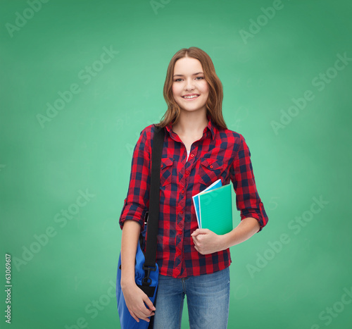 smiling female student with bag and notebooks