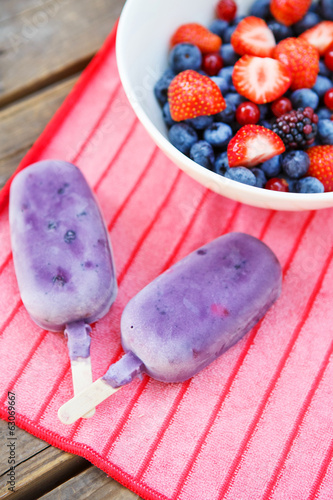 Homemade ice cream pops with different berries