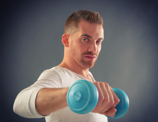 Handsome man holding dumb bells