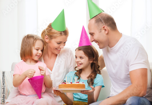 smiling family with two kids in hats with cake