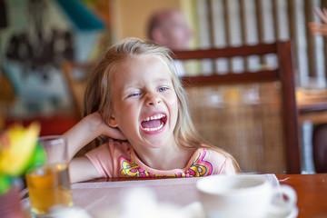 Smiling little girl having early breakfast