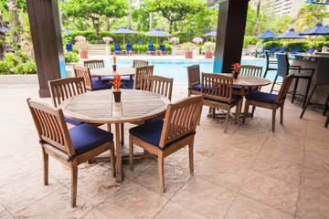 Hotel outdoor cafe with white table and chairs near pool