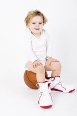 little girl playing with a basketball