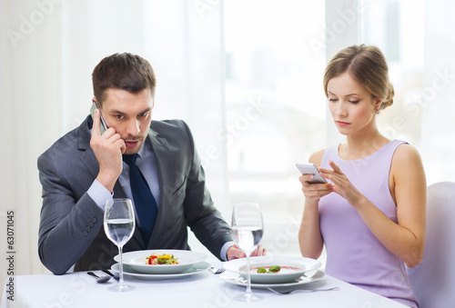 busy couple with smartphones at restaurant